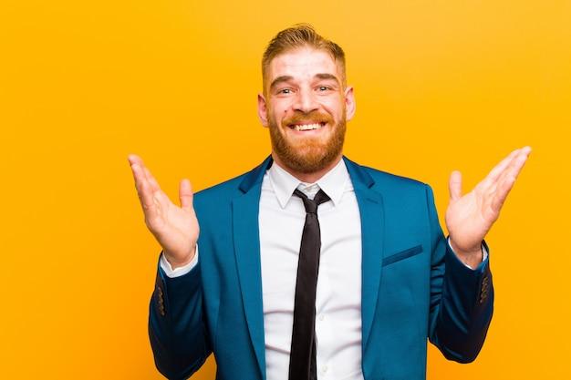 Jovem empresário de cabeça vermelha se sentindo feliz, animado, surpreso ou chocado, sorrindo e surpreso com algo inacreditável na laranja