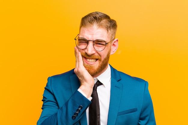 Jovem empresário de cabeça vermelha, segurando a bochecha e sofrendo dor de dente dolorosa, sentindo-se doente, infeliz e infeliz, procurando uma parede de dentista laranja