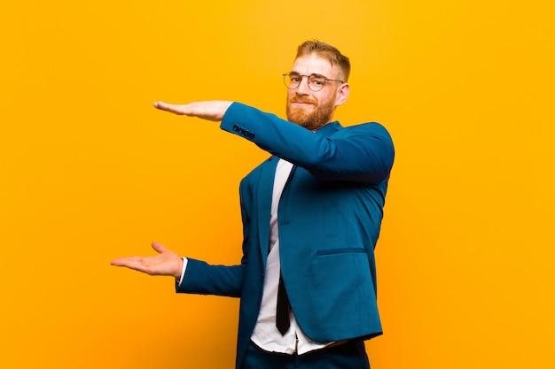 Jovem empresário de cabeça vermelha, segurando um objeto com as duas mãos no lado copyspace, mostrando, oferecendo