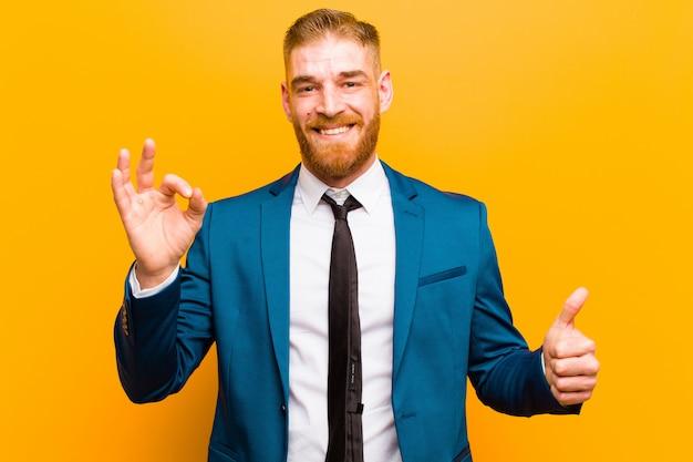 Jovem empresário de cabeça vermelha, sentindo-se feliz, espantado, satisfeito e surpreso, mostrando bem e polegares para cima gestos, sorrindo contra laranja