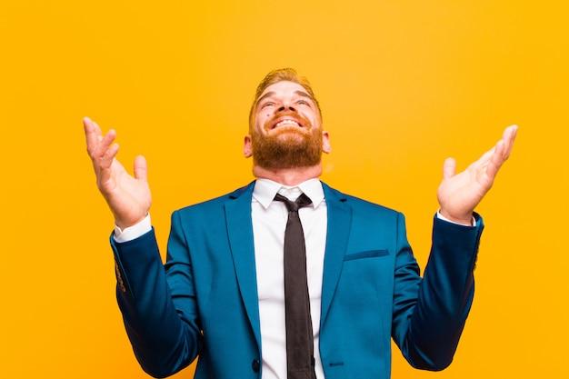 Jovem empresário de cabeça vermelha, sentindo-se feliz, espantado, sortudo e surpreso, comemorando a vitória com as duas mãos no ar contra a laranja