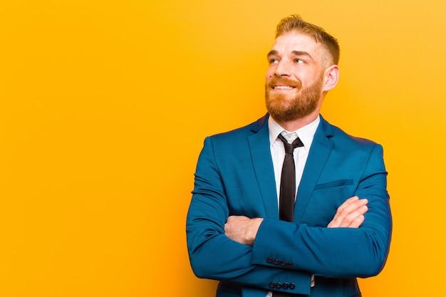 Jovem empresário de cabeça vermelha, sentindo-se feliz, orgulhoso e esperançoso, pensando ou pensando, olhando para copiar o espaço com os braços cruzados