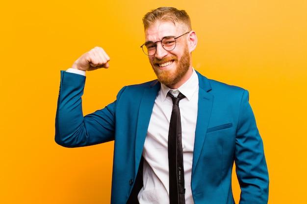 Jovem empresário de cabeça vermelha, sentindo-se feliz, satisfeito e poderoso, flexionando o ajuste e o bíceps muscular, parecendo forte após a parede da academia laranja