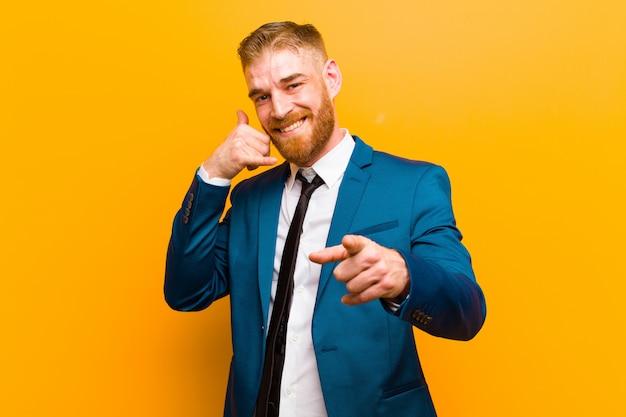 Jovem empresário de cabeça vermelha, sorrindo alegremente e apontando para a câmera enquanto faz uma ligação, gesto mais tarde, falando na parede do telefone laranja