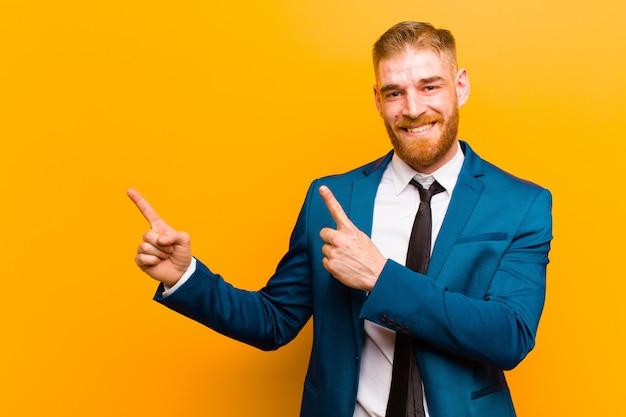 Jovem empresário de cabeça vermelha sorrindo alegremente e apontando para o lado e para cima com as duas mãos, mostrando o objeto