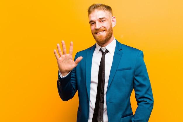 Jovem empresário de cabeça vermelha sorrindo e olhando amigável, mostrando o número cinco ou quinto com a mão para a frente, contando para baixo