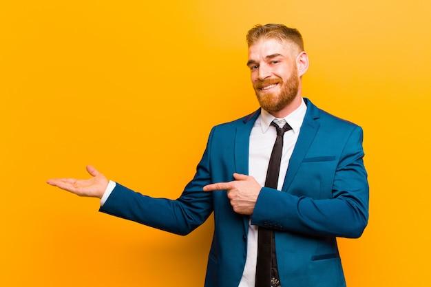 Jovem empresário de cabeça vermelha, sorrindo, se sentindo feliz, despreocupado e satisfeito, apontando para o conceito ou idéia no espaço da cópia do lado