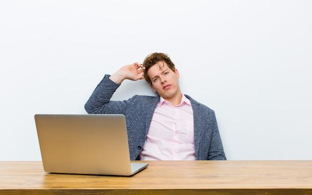 Jovem empresário de cabeça vermelha, trabalhando em sua mesa com um laptop
