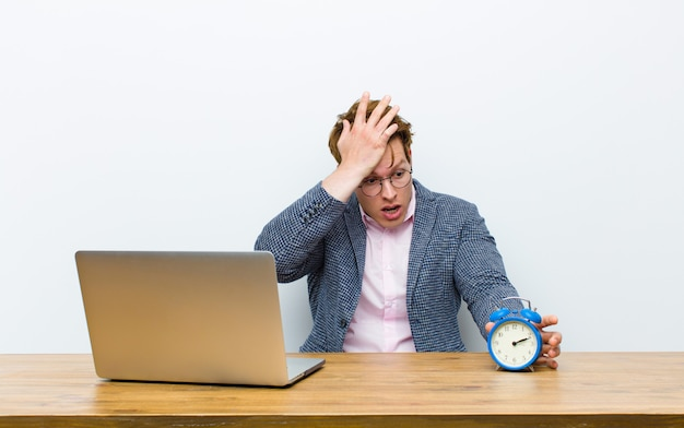 Jovem empresário de cabeça vermelha, trabalhando em sua mesa com um relógio. conceito de tempo