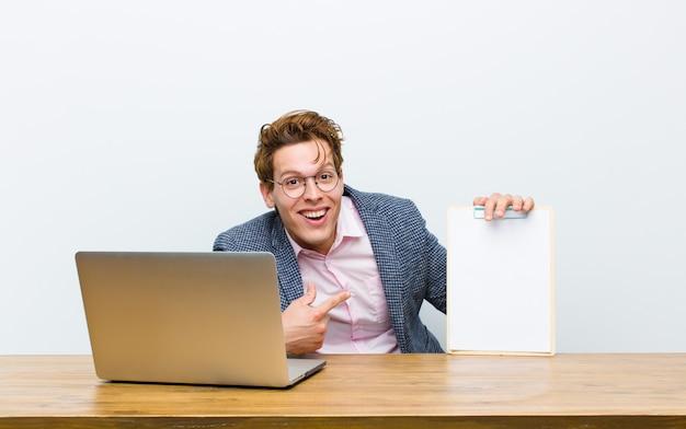 Jovem empresário de cabeça vermelha, trabalhando em sua mesa com uma folha de papel