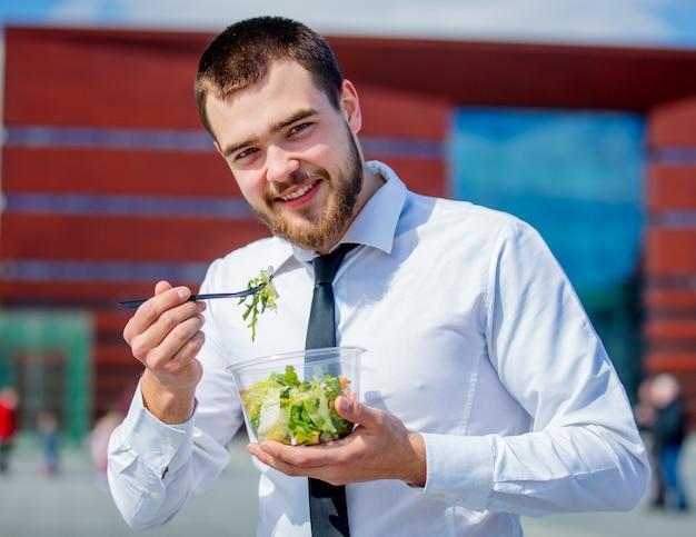 Jovem empresário de camisa e gravata com salada lancheira