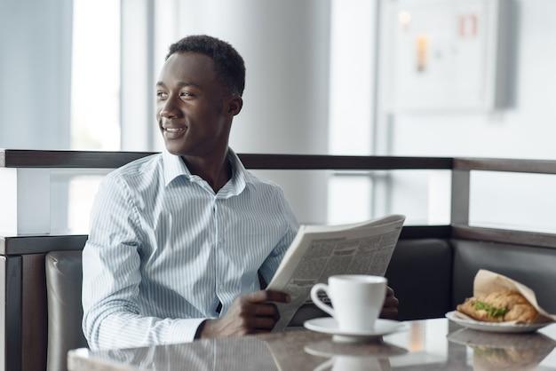 Jovem empresário de ébano com jornal, almoçando no café do escritório. empresário de sucesso bebe café na praça de alimentação, homem negro com roupa formal