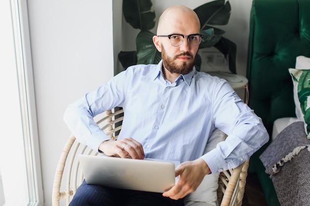 Jovem empresário de óculos com um laptop sentado em uma cadeira de trabalho remoto