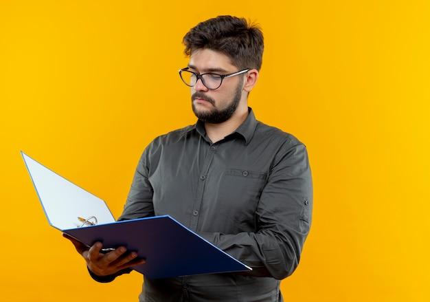 Jovem empresário de óculos segurando e olhando para uma pasta isolada em amarelo