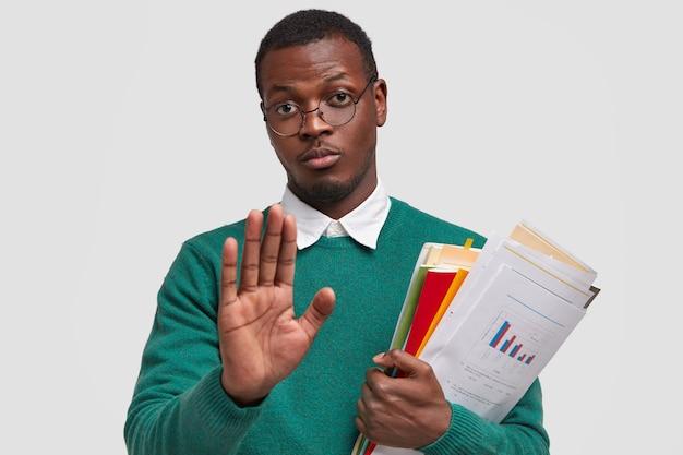 Jovem empresário de pele morena descontente, segura documentação e bloco de notas, demonstra gesto de pare, recusa-se a desenvolver ideias de negócios sozinho
