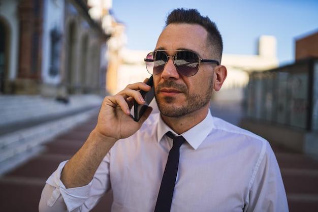 Jovem empresário de sucesso com uma roupa formal e óculos de sol, falando ao telefone