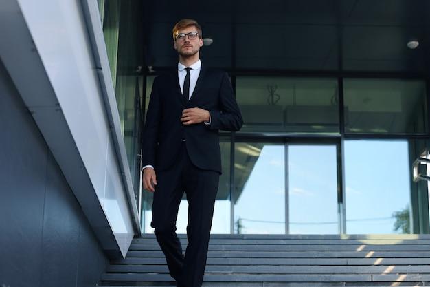 Jovem empresário de sucesso descendo as escadas do lado de fora do prédio de escritórios.