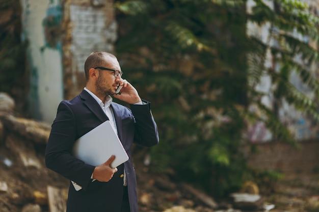 Jovem empresário de sucesso em camisa branca, terno clássico, óculos. homem de pé com o computador laptop pc, falando no telefone perto de ruínas, destroços, edifício de pedra ao ar livre. escritório móvel, conceito de negócio.