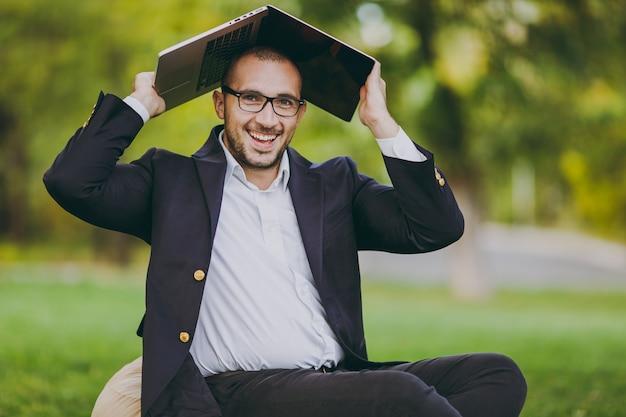 Jovem empresário de sucesso em camisa branca, terno clássico, óculos. homem sente-se no pufe macio sob a cobertura laptop pc computador no parque da cidade, no gramado verde ao ar livre na natureza. escritório móvel, conceito de negócio.
