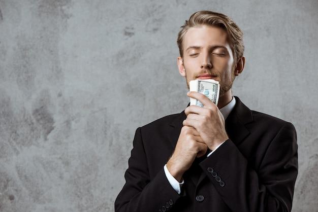 Jovem empresário de sucesso em terno segurando dinheiro