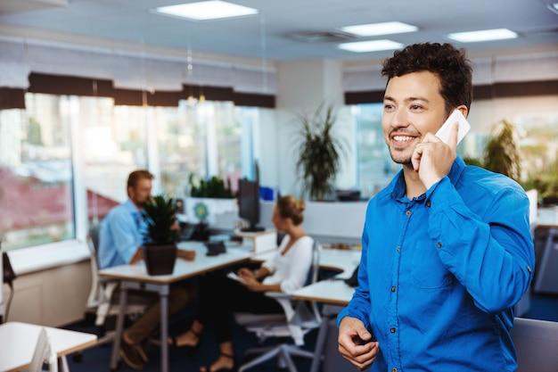 Jovem empresário de sucesso, falando no telefone, sorrindo, sobre o escritório