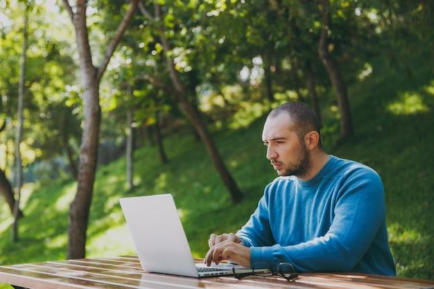 Jovem empresário de sucesso inteligente ou estudante de óculos casual camisa azul, sentado à mesa com o telefone celular no parque da cidade, usando laptop, trabalhando ao ar livre na natureza verde. conceito de escritório móvel.