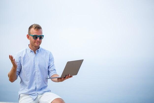 Jovem empresário de sucesso masculino trabalhando com laptop de férias à beira-mar. ele usa óculos escuros, camisa e shorts brancos. trabalho fora do escritório, freelancer