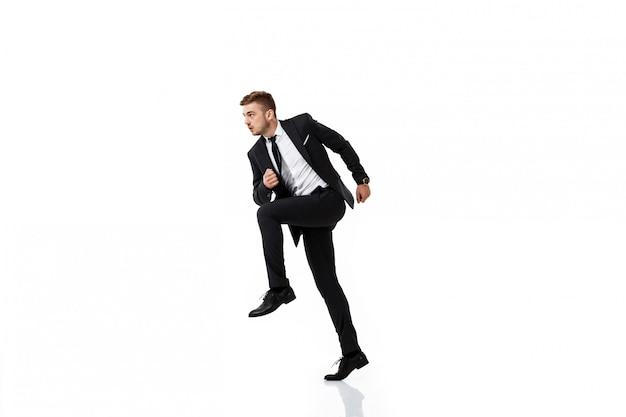 Jovem empresário de sucesso no terno correndo.