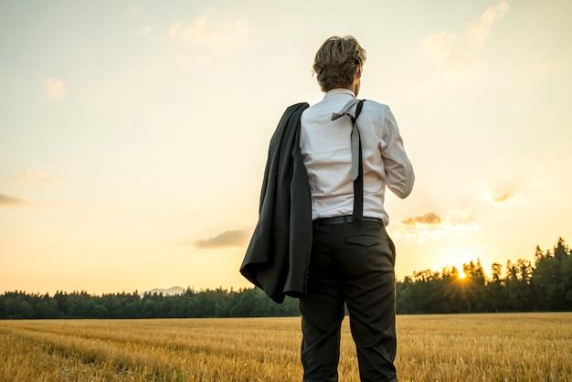 Jovem empresário de sucesso permanente no campo de trigo, olhando para o futuro