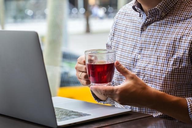 Jovem empresário de sucesso sentado em um café, bebendo chá vermelho saudável e trabalhando em um laptop. composição de estilo de vida com luz natural