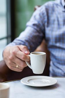 Jovem empresário de sucesso sentado em um café e bebendo café da manhã. composição de estilo de vida com luz natural