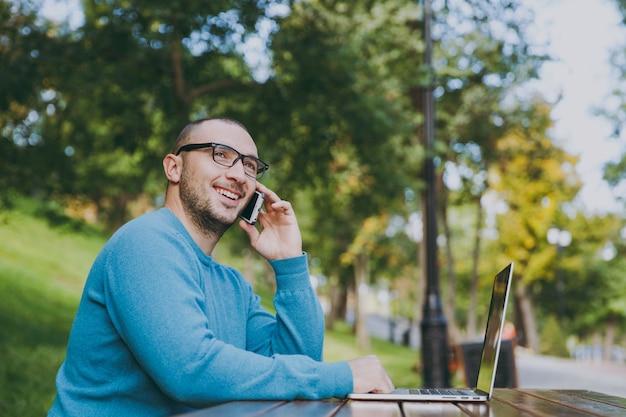 Jovem empresário de sucesso sorridente homem inteligente ou estudante em casual camisa azul, óculos, sentado à mesa, falando no celular no parque da cidade usando laptop, trabalhando ao ar livre. conceito de escritório móvel.