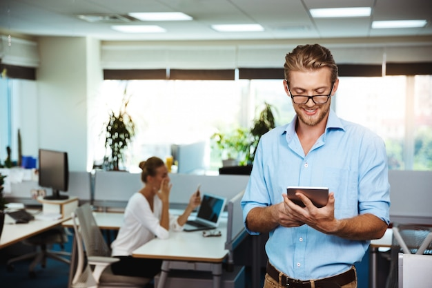 Jovem empresário de sucesso, sorrindo, olhando para tablet, escritório