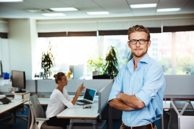 Jovem empresário de sucesso, sorrindo, posando com os braços cruzados, sobre o escritório
