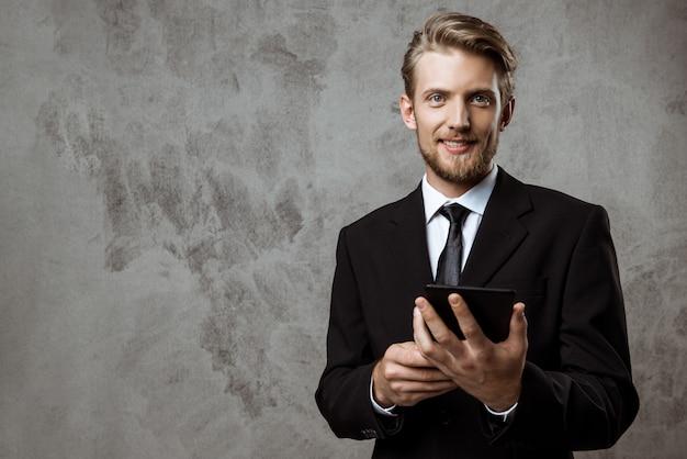 Jovem empresário de sucesso sorrindo, segurando o tablet