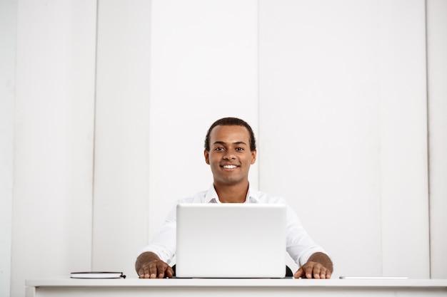 Jovem empresário de sucesso, sorrindo, sentado no local de trabalho com o laptop