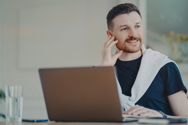Jovem empresário de sucesso usando fones de ouvido olhando para o lado, sentindo-se feliz e sorrindo após a reunião online. freelancer pensando no resultado positivo da conversa enquanto trabalha no laptop em casa