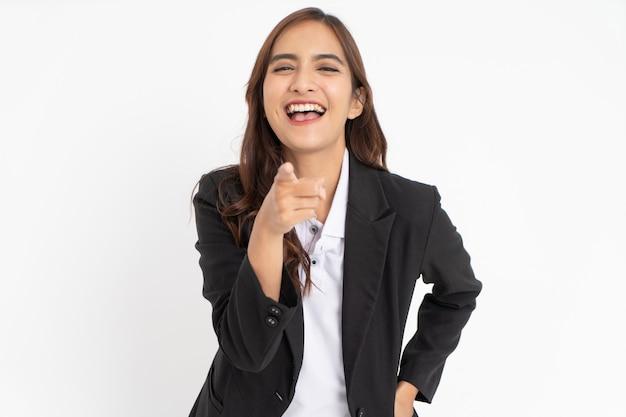 Jovem empresário de terno apontando para a câmera com expressão ofensiva de riso