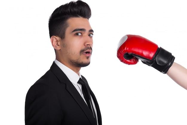 Jovem empresário de terno é atingido por uma pessoa em luvas de boxe. agressão empresarial