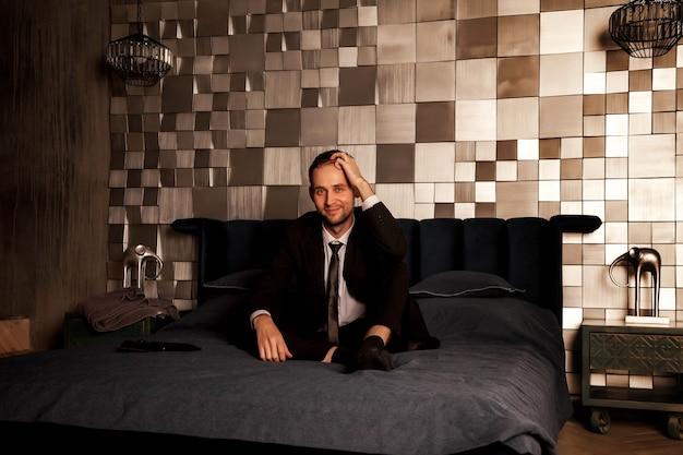 Jovem empresário de terno está sentado na cama no quarto, segurando a mão na cabeça. o gesto de uma pessoa indica declínio criativo, apático ou depressão. conceito de emoções humanas. copie o espaço