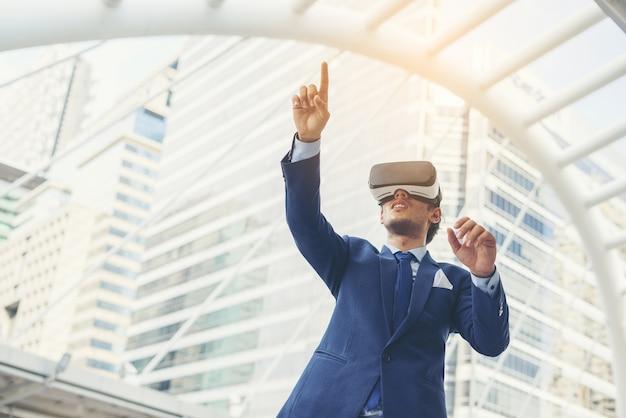 Jovem empresário de terno preto que usa óculos de realidade virtual.
