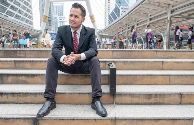 Jovem empresário desempregado sentado em uma escada na cidade