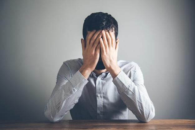 Jovem empresário desesperado encostado na mesa