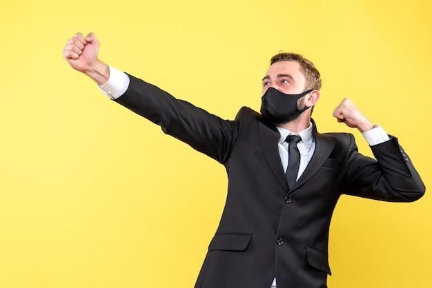 Jovem empresário dinâmico mostrando sua alegria e motivação sobre o amarelo isolado