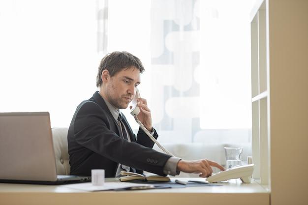 Jovem empresário discando um número de telefone