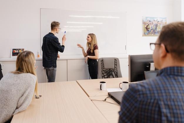 Jovem empresário discutindo com os colegas sobre o quadro branco no escritório