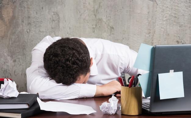Jovem empresário dormindo na mesa do escritório.