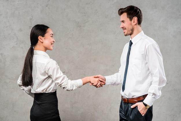 Jovem empresário e empresária apertando a mão um do outro contra a parede cinza