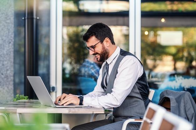 Jovem empresário elegante caucasiano positivo de terno com óculos, sentado no café e digitando no laptop seu relatório.
