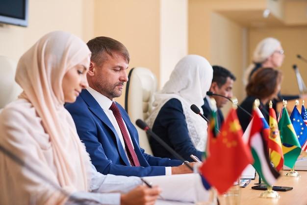 Jovem empresário elegante e confiante em trajes formais sentado entre seus sócios estrangeiros e outros palestrantes na conferência